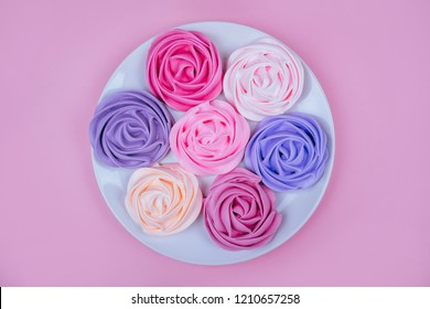 Beautiful pink, magenta, orange and violet rose flower shaped meringue flatlay on the white round plate.