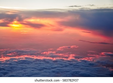 Beautiful pink and orange clouds at dawn morning sunlight. View from the plane.