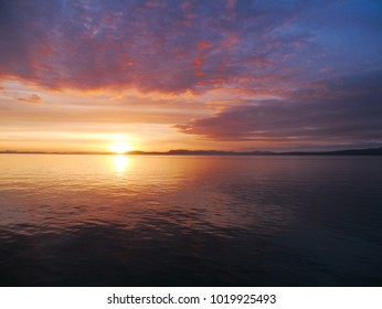 Beautiful pink and orange sunset in Alaska waters - amazing contrast with sunset and clounds