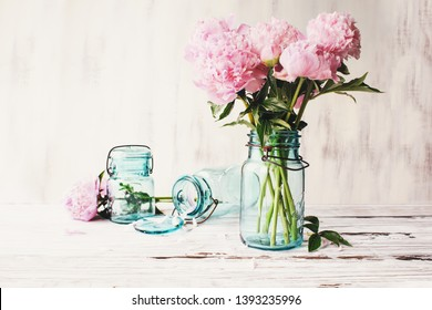 Beautiful pink Peony flowers in an antique blue mason jar over a white rustic wood table background  with copy space for your text. Image edited to give farmhouse decor style.