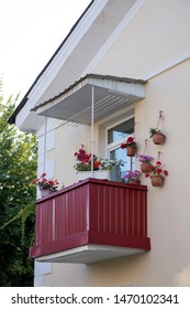 Beautiful pink petunias on the balcony. Flower arrangement and decoration of the balcony with flowers. White wall of a traditional home in Portugal. Floriculture and gardening.
