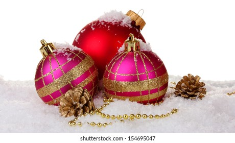 beautiful pink and red Christmas balls and cones on snow isolated on white