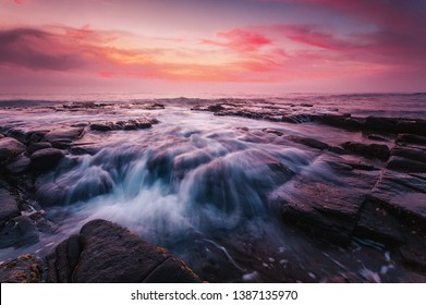 Beautiful pink red dawn skies with a sea mist wandering onshore creating a mystical effect and ocean waves spectacularly flow over the tessellated rocks of Garie Beach Australia.