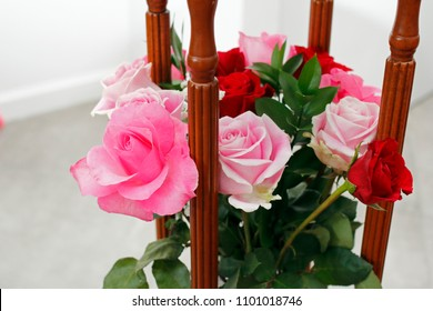 Beautiful pink and red roses flowers bouquet in between four wooden columns of a side table. Pink and red roses flowers with four wooden table columns close-up