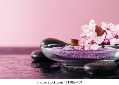 Beautiful pink Spa Flowers on Spa Hot Stones on Water Wet Background. Side Composition. Copy Space. Spa Concept. Pink Background.