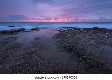Beautiful pink sunlight paints the cloudy sky looking across the Indian Ocean at sunrise from a rocky beach.