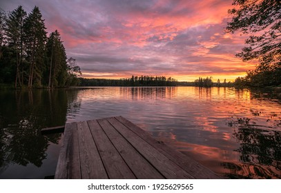 Beautiful pink sunset on a forest lake, wooden bridge for fishing