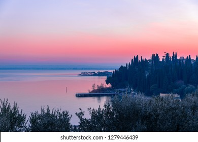 Beautiful pink sunset on Lake Garda. View of the embankment and piers of the city of Sirmione. Winter time on the lakes of Italy.