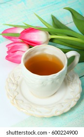 Beautiful pink tulips and a cup of tea on a blue wooden background.