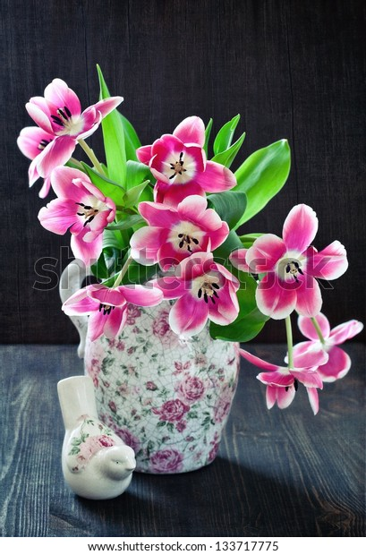 Beautiful pink tulips in a jar on a wooden table.