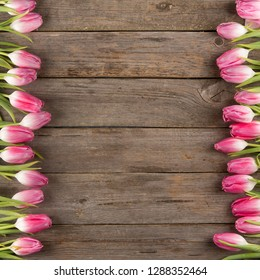 Beautiful pink tulips on wooden background. Top view, copy space. Space for text. Postcard template