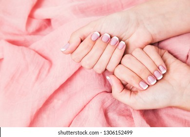 Beautiful pink and white french manicure. Top view of two female hands isolated on fabric soft background. Horizontal color photography.