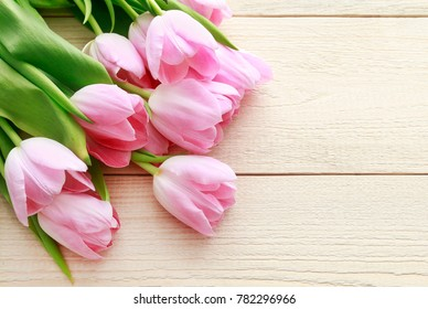 Beautiful pink and white tulips on wooden background. Copy space.