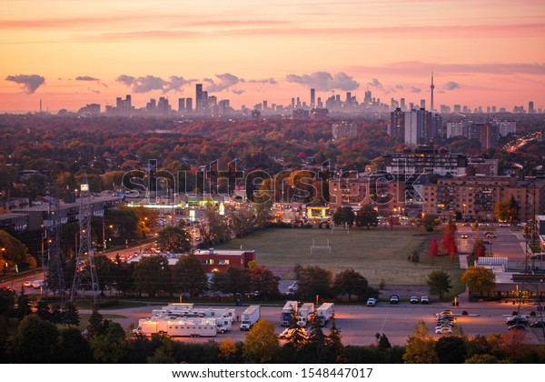 Beautiful pink yellow red purple morning sky clouds in Toronto city, Canada. Rays of early rising sun. Landscape aerial top view with urban street. Twilight in Canadian town at sunrise or sunset.