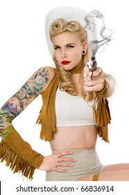 Beautiful pinup model dressed a cowgirl shooting a gun