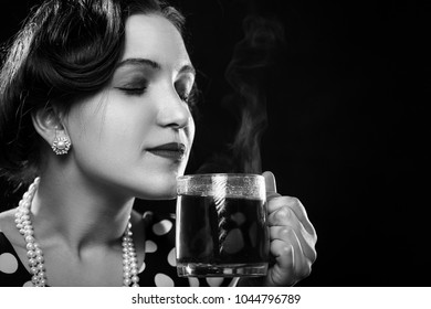 beautiful pinup woman with cup of tea on black background with copy space smell smiling, monochrome