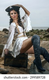 Beautiful pirate woman sitting on the beach with a classic pistol in her hand