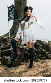 Beautiful pirate woman standing near treasure chest on the beach