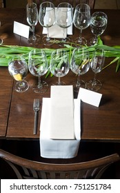 A beautiful place setting with blank menu and place card surrounded by lush greenery and clear wine glasses.