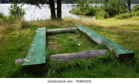 Beautiful place with wood benches for a camping and looking a wonderful lake with forest.