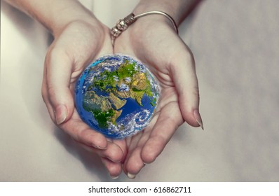 Beautiful planet Earth in female hands. Elements of this image furnished by NASA
