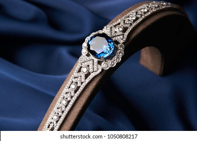 Beautiful platinum bracelet. Luxury women bracelet with diamonds and sapphire on blue silk background, close-up
