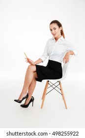 Beautiful playful businesswoman sitting on the chair and holding pencil isolated on a white background