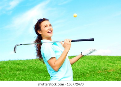 beautiful playful female golfer relaxing throwing ball in the air laughing and holding golf club against clear blue sky.
