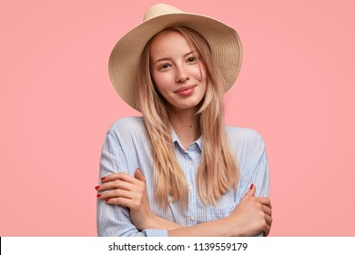 Beautiful pleased shy young female model keeps hands crossed, looks positively at camera, wears hat and shirt, isolated over pink background. Fashionable European woman tourist has excursion