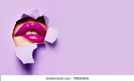 Beautiful plump bright lips of pink color peep into the slit of colored paper.Cosmetics, make-up, beauty salon, make-up artist, lilac lip gloss, beautiful teeth, sales.Fashion, beauty, make-up.