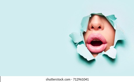 Beautiful plump bright lips of pink color peep into the slit of colored paper.make-up, makeup, advertising, facial, boutique, smooth skin, emotions, surprise.