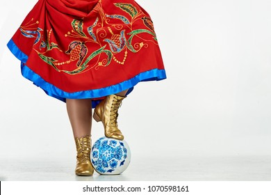 Beautiful plump girl with braid in national Russian dress posing with a soccer ball on cyclorama