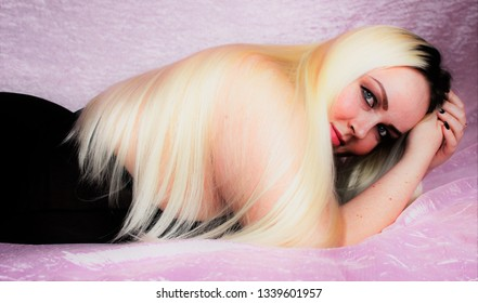 Beautiful plump woman with long white hair lying on the bed. Chic blonde large size XXXL very much loves himself and his body.