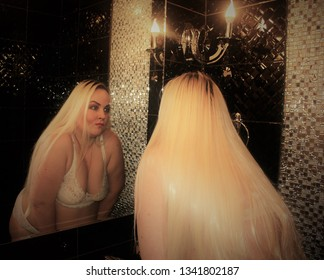 A beautiful plump woman with long white hair stands in the way of a mirror. Gorgeous blonde big size XXXL is very pleased with herself.
