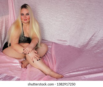 Beautiful plump woman with long white hair in black underwear sitting on a bed. Gorgeous blonde big size XXXL is very pleased with herself.