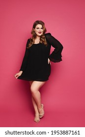 A beautiful plump woman with makeup in pin-up style wearing black short dress posing against a pink background