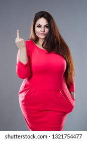 Beautiful plus size fashion model in red dress, fat woman with long hair showing finger sign on gray background, studio shot