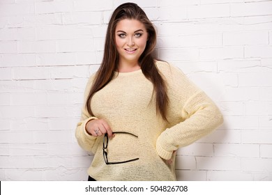 Beautiful plus size female model posing in studio.