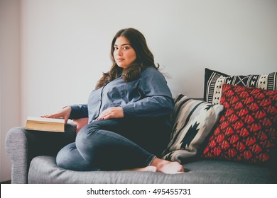 Beautiful plus size girl sitting on sofa reading a book. Toned picture