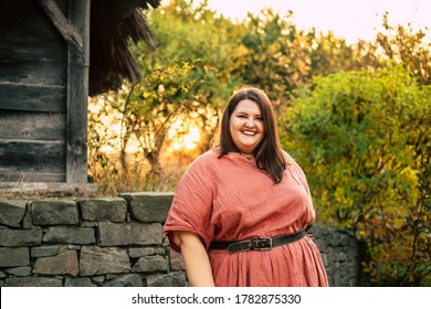Beautiful plus size model in red dress with leather belt, standing outdoors near stone fence