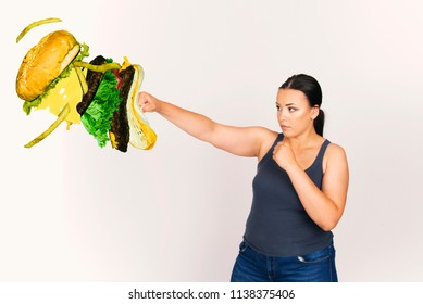 beautiful plus size model young woman kicking off hamburger, junk food concept