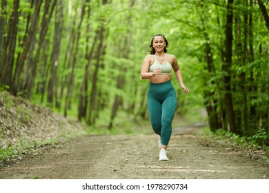 Beautiful plus size runner woman running on a dirt road in the forest