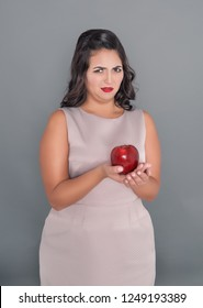 Beautiful plus size woman do not want apple on gray background. Diet concept