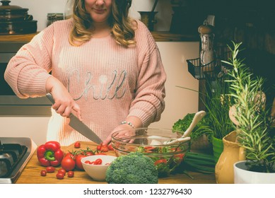 Beautiful plus size woman is making fresh salad in the kitchen