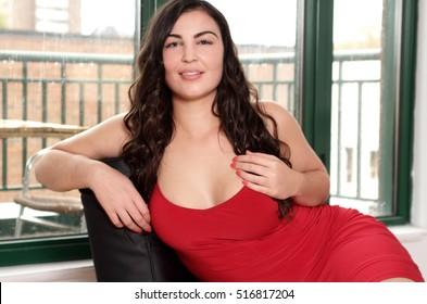 Beautiful plus size woman in red dress portrait sitting in luxury suite