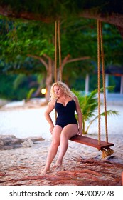 beautiful plus size woman sitting on tree swings, summer vacation