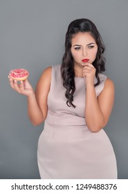 Beautiful plus size woman thinking about eating donut. Overweight concept