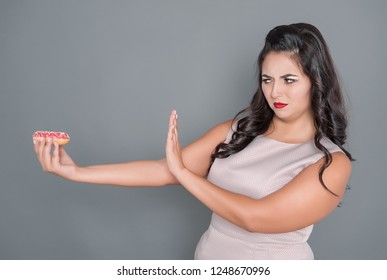 Beautiful plus size woman don't want eat donut. Overweight concept