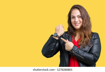 Beautiful plus size young woman wearing a fashion leather jacket over isolated background In hurry pointing to watch time, impatience, upset and angry for deadline delay