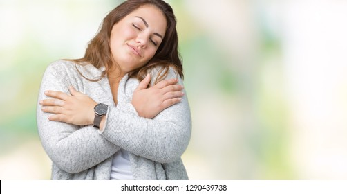 Beautiful plus size young woman wearing winter jacket over isolated background Hugging oneself happy and positive, smiling confident. Self love and self care
